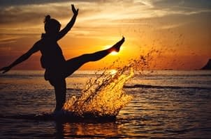 A woman being in the present moment by splashing water in a calm sea at sunset
