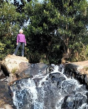Chantaul Jordan standing at the top of a waterfall.
