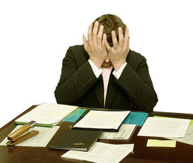 Picture of a man sitting by his desk and looking stressed
