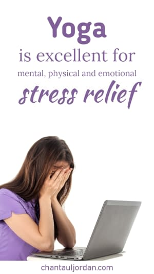 A woman in front of a laptop holding her hands on her face due to stress