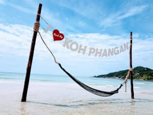 A hammock suspended above calm and clear water on a sunny white beach.